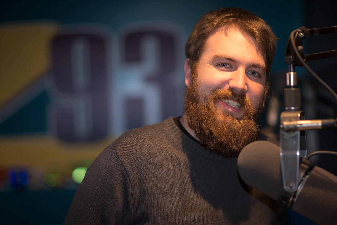 Local radio host Jesse standing behind microphone